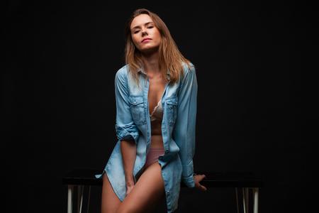 Ritratto di una giovane ragazza con una camicia di jeans e belle gambe seduta su un tavolo in uno studio buio