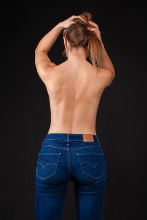 Rückansicht, junge Frau in Denim-Jeans gegen das dunkle Wandstudio