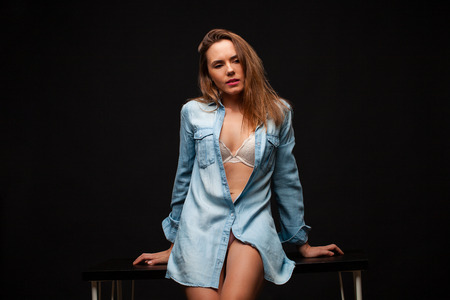 Portrait of a young girl in a denim shirt and beautiful legs sitting on a table in a dark studio