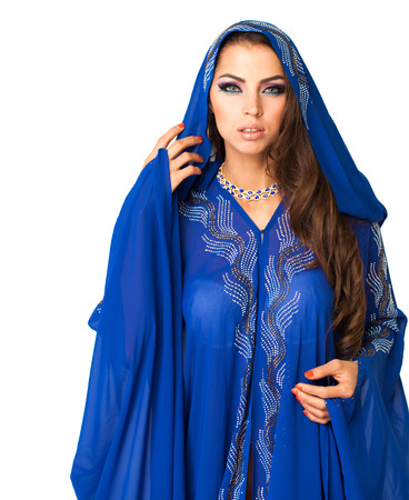 Young arabic woman in long blue dress, isolated on white background Фото со стока