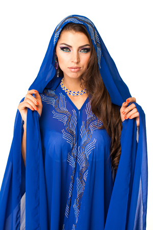 Young arabic woman in long blue dress, isolated on white background Stockfoto