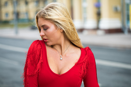 Portrait close up of young beautiful blonde woman in red sexy dress, spring street outdoors