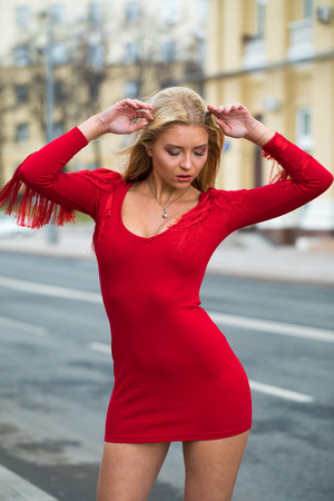 Portrait close up of young beautiful blonde woman in red dress, spring street outdoors