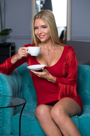 Beautiful young blonde girl in a red sexy dress sitting on a sofa in a beauty salon Stock Photo