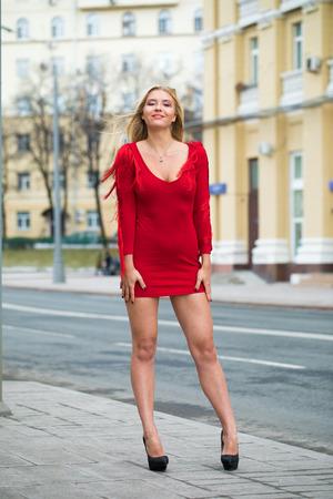Portrait gros plan de la belle jeune femme blonde en robe rouge, rue du printemps à l'extérieur