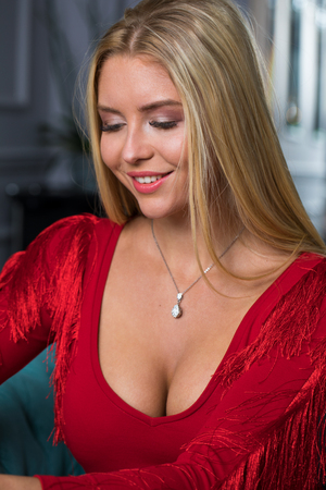 Beautiful young blonde girl in a red sexy dress sitting on a sofa in a beauty salon Standard-Bild