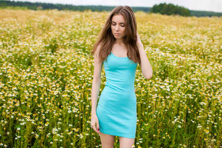 Portrait close up of a beautiful young woman in turquoise tight clothes in a chamomile field