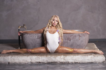 Sexy blonde woman in white bathing suit posing in a bath in sequins