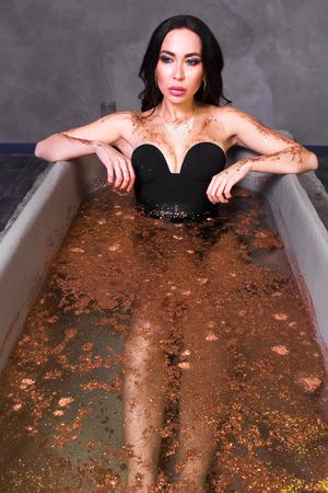 Sexy brunette woman in black kombi dress posing in a bath in sequins