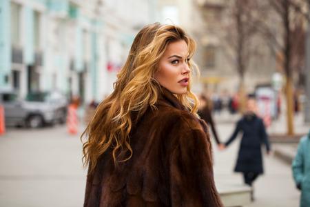 Mooie jonge blonde vrouw in nertsbontjas die herfststraat loopt