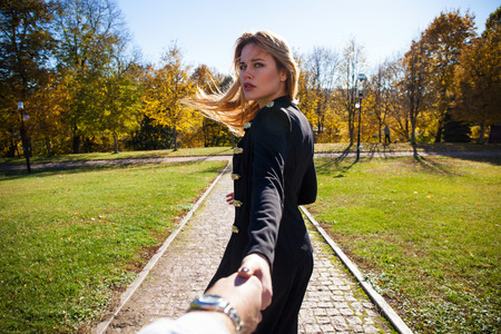 Follow me. Beautiful young blonde and holding the hand of unidentified man and walking with him on sunny autumn park