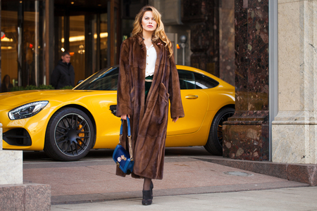 Portrait of a full length young blonde woman in mink winter fur coat and posing outdoors in autumn street