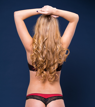 Back view. Sexy blonde woman in red underwear on a dark blue wall studio