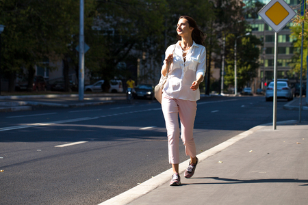 Portrait in full growth, young beautiful brunette woman in white blouse and pink pants walking on the street, summer outdoors Фото со стока