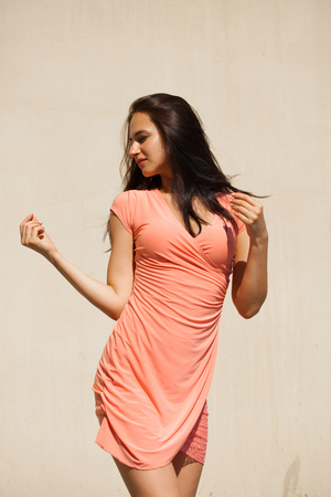 Happy Beautiful young brunette woman in sexy pink dress, against white wall Imagens