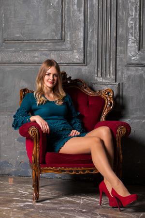 Full length of a beautiful blonde woman in short blue dress, posing on dark wall studio background