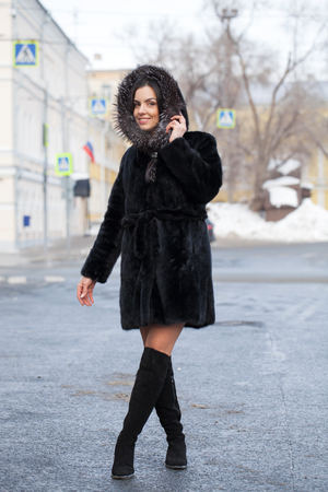 Full body. Young beautiful brunette woman in fur mink coat posing on winter park. Model wearing stylish warm clothes.