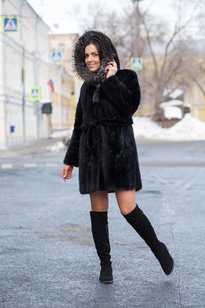 Full body. Young beautiful brunette woman in fur mink coat posing on winter park. Model wearing stylish warm clothes. Standard-Bild - 116350607