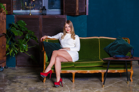 Full length of a beautiful blonde sexy woman in white knitted dress sitting in green armchair in dark studio