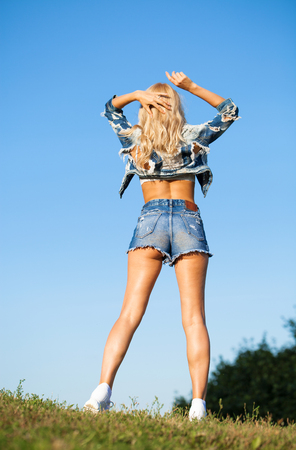 Beautiful blonde woman dressed in a denim jacket and shorts. Fashion model in jeans clothing. Summer park outdoor