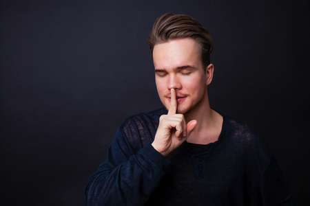 Young man showing silence gesture on the dark background.