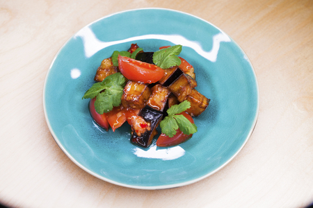 Salad of tomatoes and fried eggplant with sauce on a blue plate