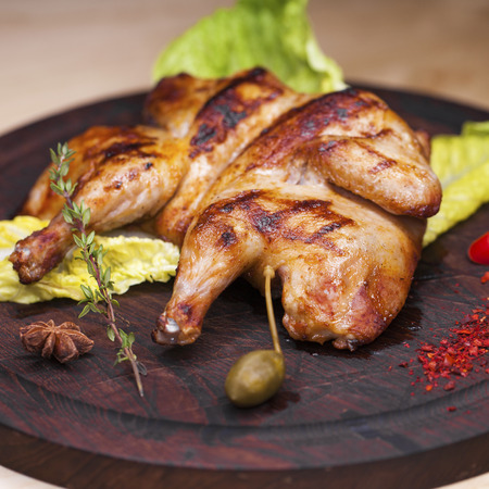 Restaurant dish, Roast chicken and leaf lettuce on a wooden board