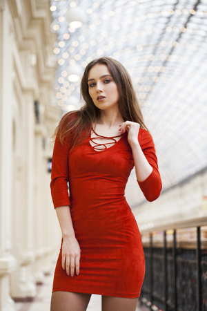 Close up portrait women. Young beautiful brunette model in red dress, indoor shop