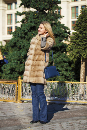 Portrait of a full length young blonde woman in mink winter fur coat and blue jeans, outdoors in autumn street