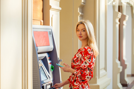 Young happy brunette woman withdrawing money from credit card at ATM Foto de archivo