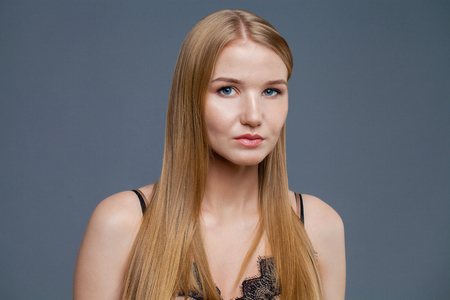 Beautiful fashion sexy blonde woman posing at studio isolated on gray background 免版税图像