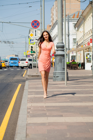 Portrait in full growth, young beautiful brunette woman in pink dress walking on the street, summer outdoors
