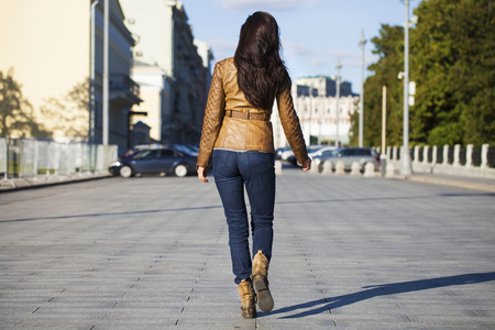 Street fashion image of young brunette woman in blue jeans and brown leather jacket