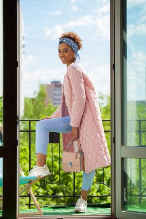 Porträt einer afrikanischen Modellfrau in rosafarbener Frühlingsjacke und blauer Hose, die auf dem Balkon posiert (Hintergrund des Fensters)