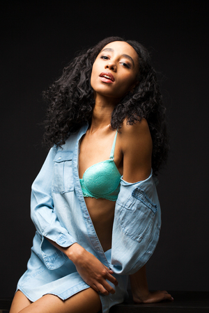 Sexy beautiful african american woman posing in blue shirt, Dark Studio shot.