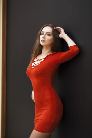 Close up portrait women. Young beautiful brunette woman in red dress against a black wall, indoors Banco de Imagens - 118762722
