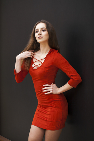 Close up portrait women. Young beautiful brunette woman in red dress against a black wall, indoors Stock fotó