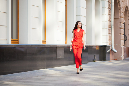 Portrait in full growth of a beautiful young woman in red suit, street summer outdoors