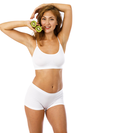 Young beautiful woman in sports underwear holds two slices of kiwi, isolated on white background