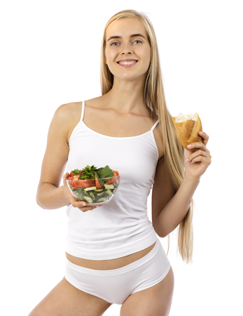 Young sexy blonde woman in white sporty wear with vegetable salad isolated on white background