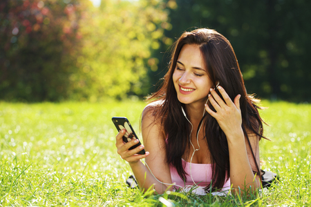Young beautiful woman in dress lies on green grass and listens to music in headphones through smartphone. Banque d'images - 119187311