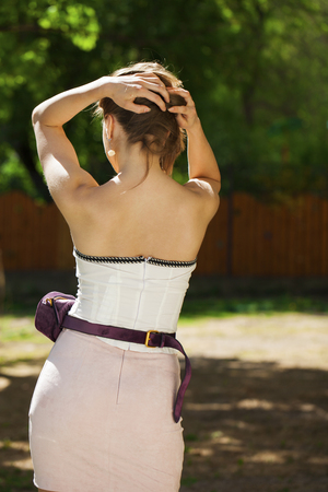 Street fashion. Closeup portrait of a happy young brunette woman in pink skirt and white corset, summer outdoors 免版税图像