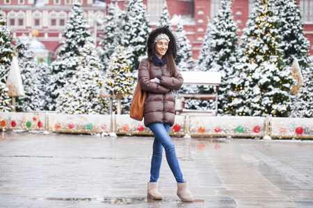 Portrait of a young brunette woman in down jacket on a red square in the center of Moscow