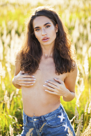 Attractive brunette young woman posing flirty topless at grass fields, summer outdoor