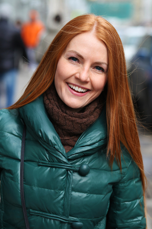 Close up portrait of pretty sexy young red hair woman in green down jacket posing on spring street