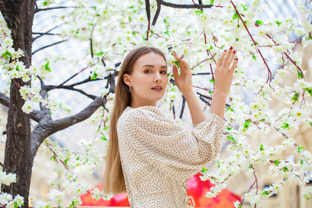 Close up, Young beautiful blonde woman in white blouse in spring flowers cherry