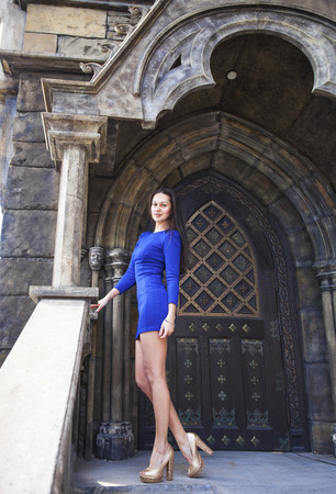 Full-length portrait young beautiful brunette woman in blue dress posing against the backdrop of an old castle in the Gothic style Banque d'images - 120791569
