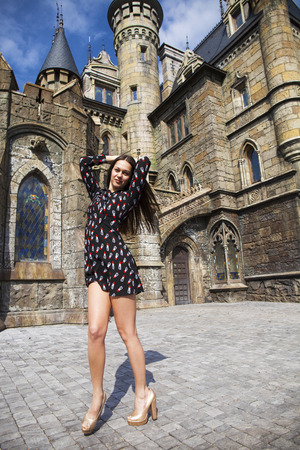 Full-length portrait young beautiful woman in summer dress posing against the backdrop of an old castle in the Gothic style