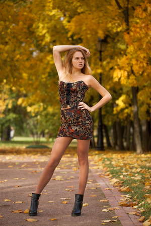 Full body, Young beautiful blonde woman in sexy dress on the autumn park