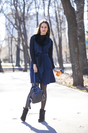 Full body. Portrait of a young beautiful woman in blue coat with a bag walking in spring park Banco de Imagens - 120993146